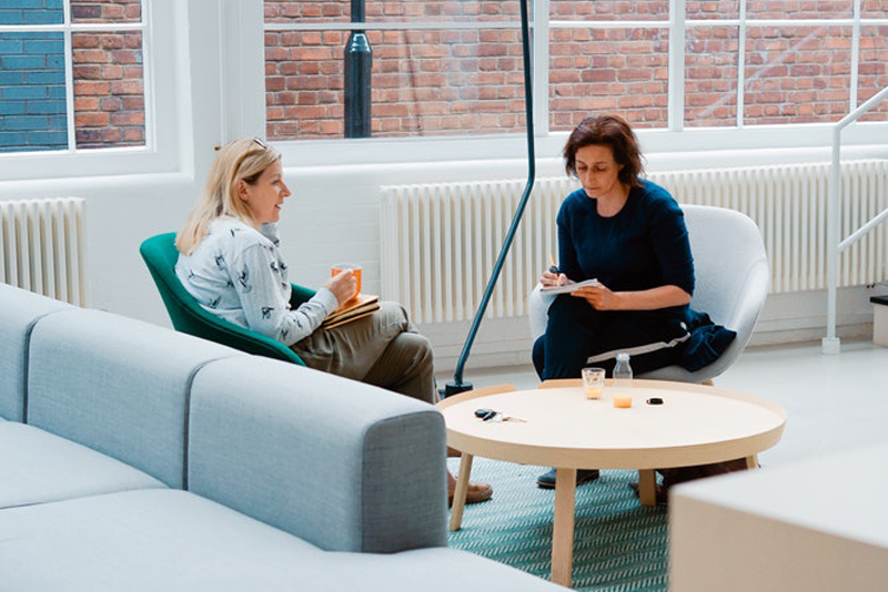 Two Women Sitting Close And Discussing Things A Therapist