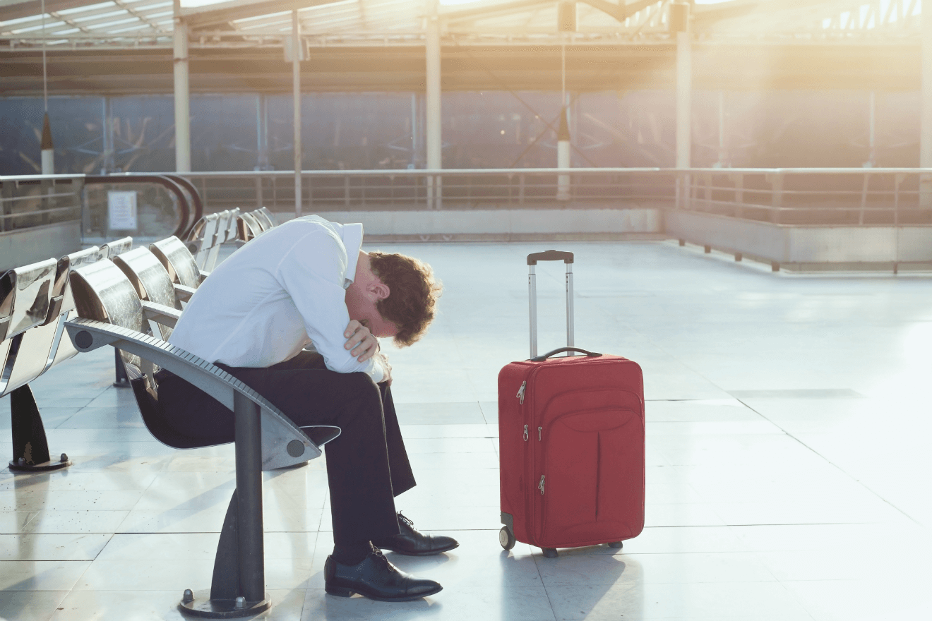 depressed man airport red suitcase