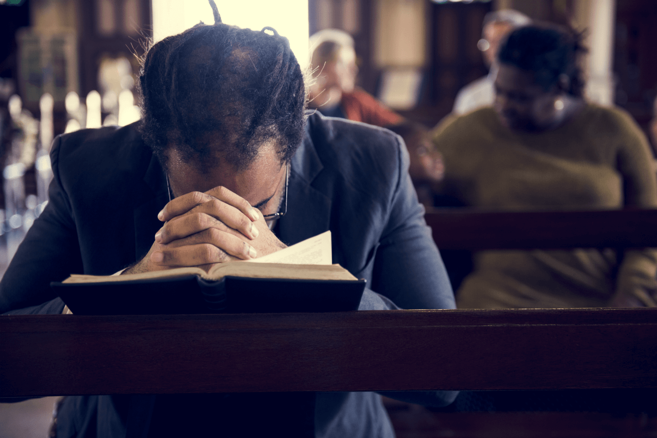 man praying church bible