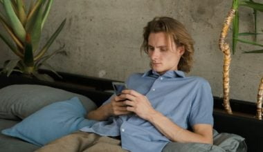 A guy looking at his phone while leaning back on a sofa