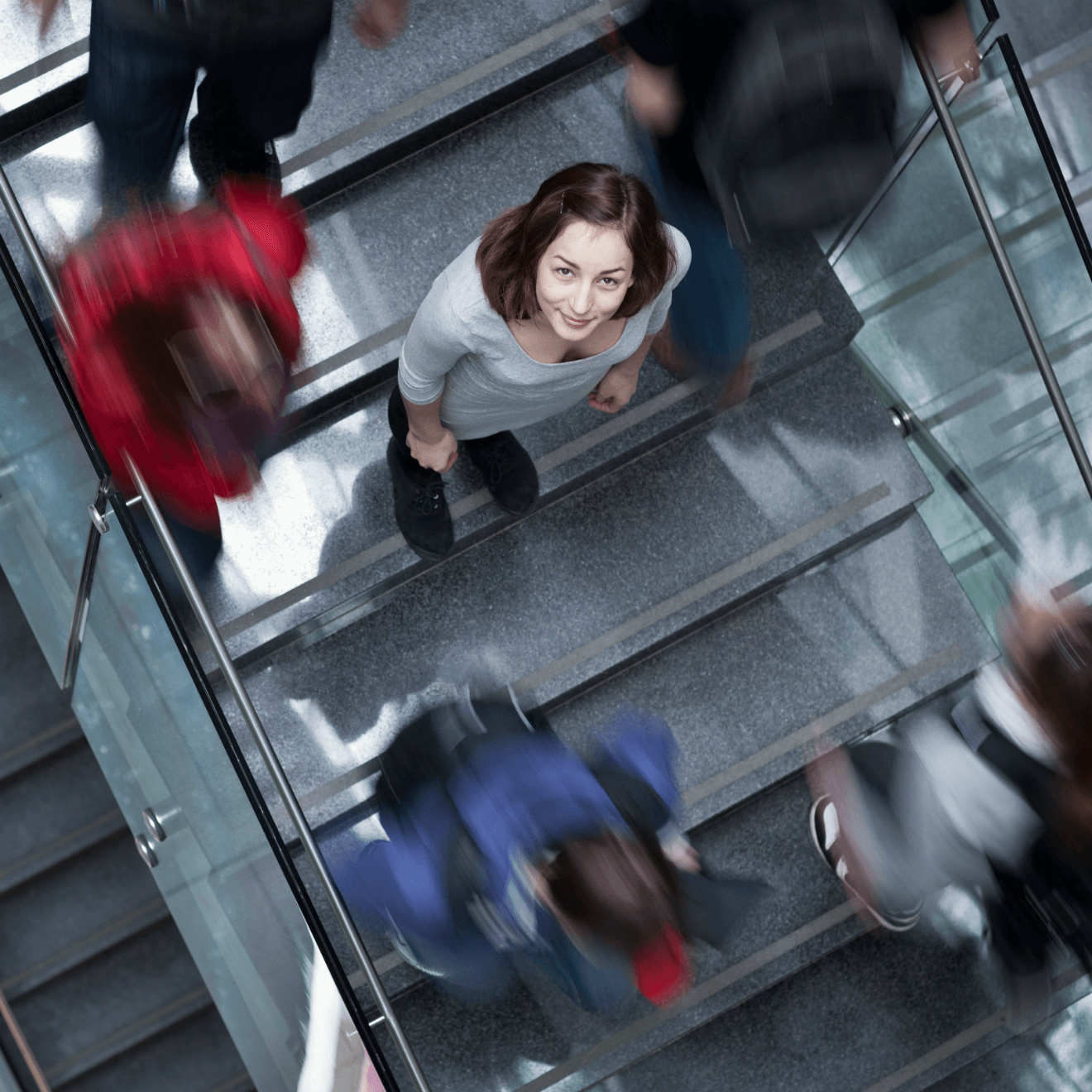 woman standing on stairs in crowd looking up at camera