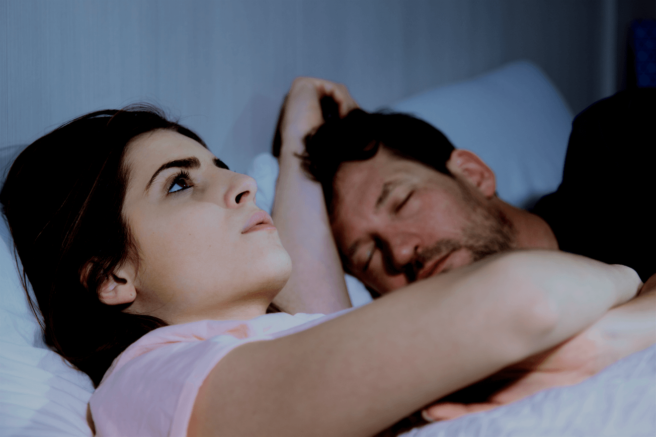 woman up in bed with husband sleeping
