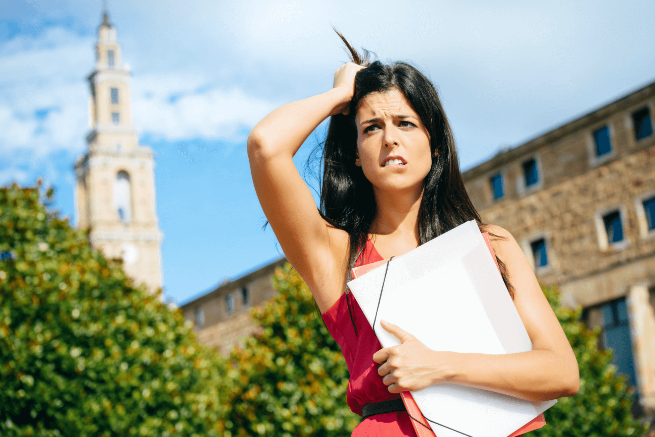 female college student stressed grabbing hair holding binder