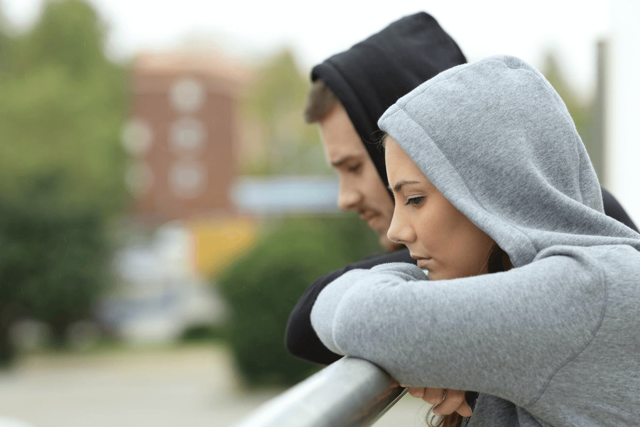 couple wearing hoodies leaning on bridge railing