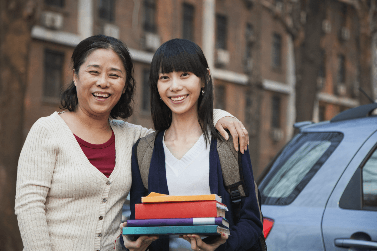Asian mom daughter holding college books near car