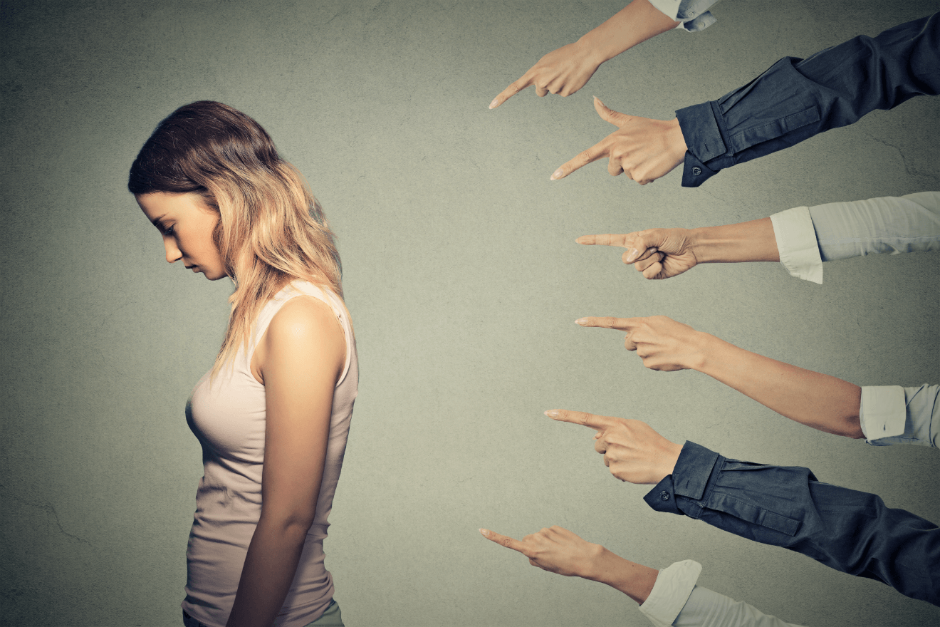 people pointing fingers at sad woman with back turned