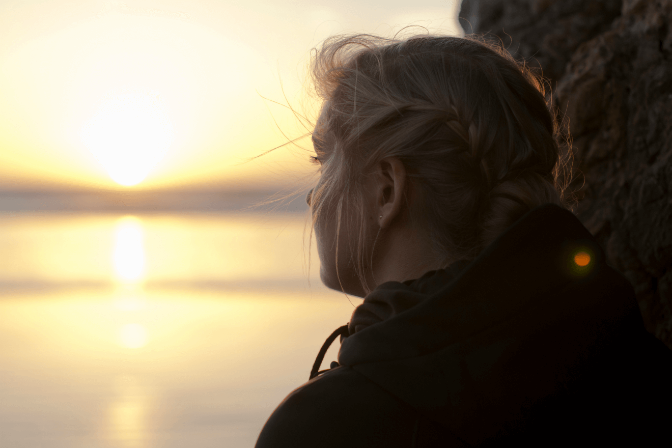 sad woman looking into sunset