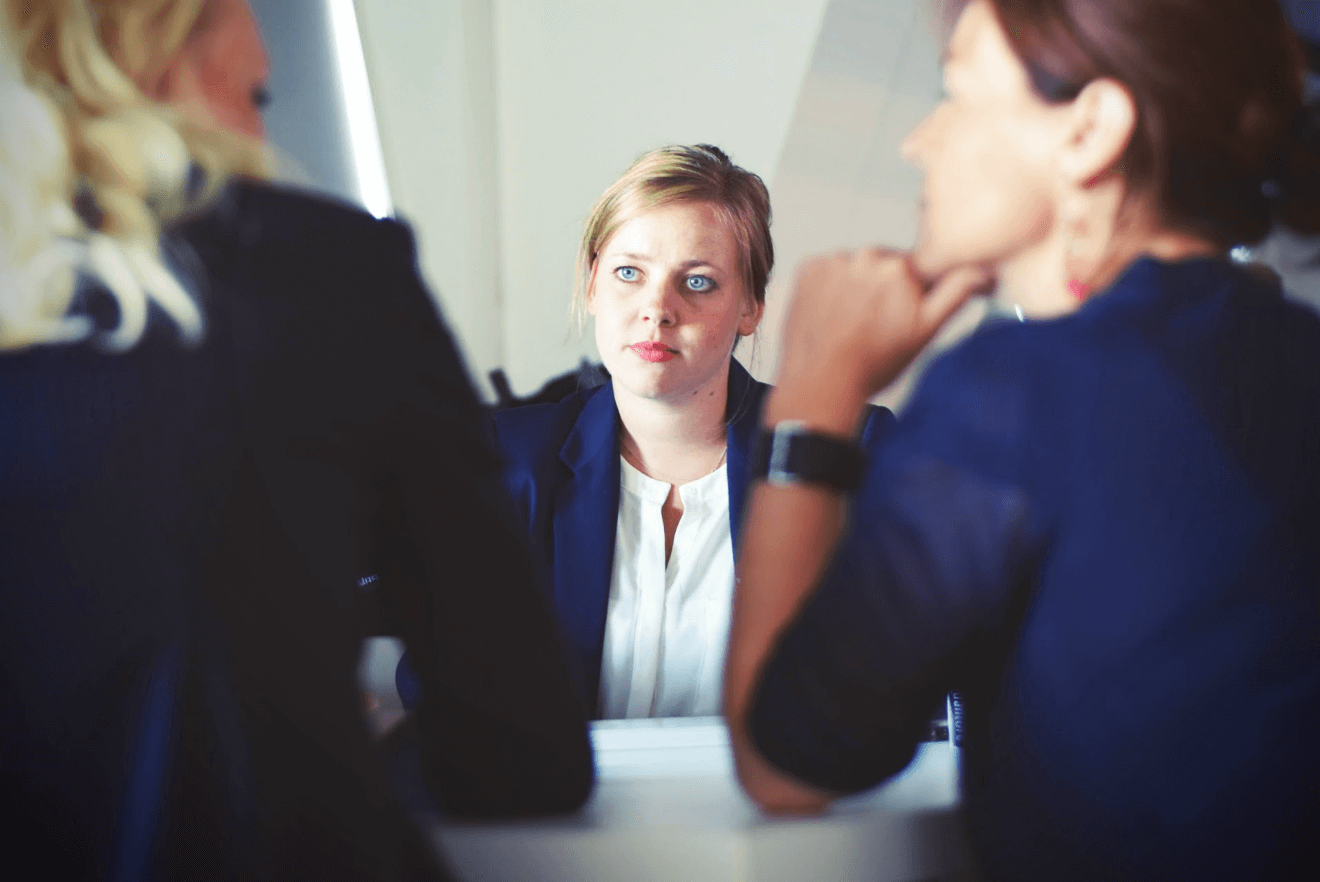 anxious woman at conference table with co-workers