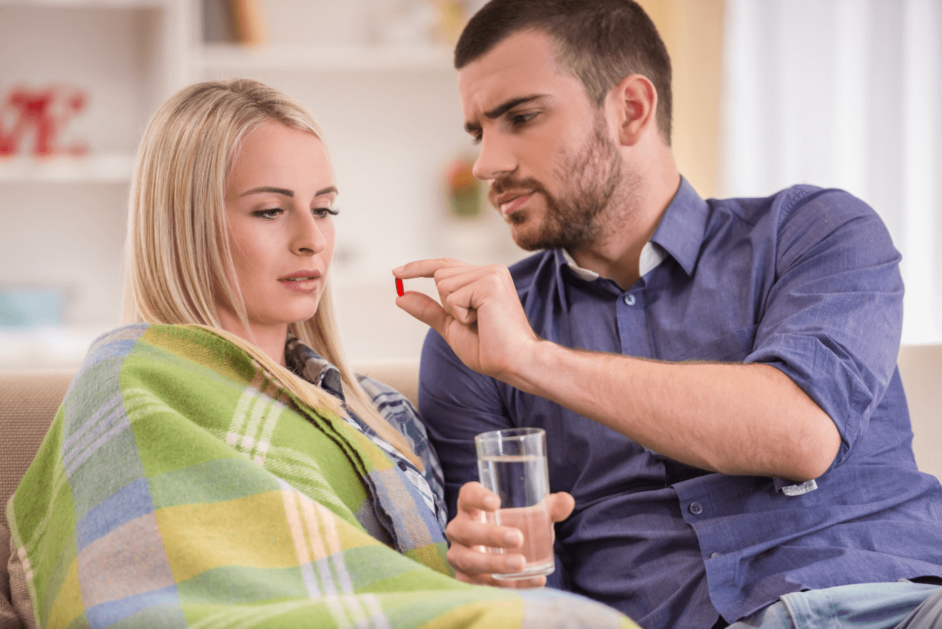 couple man giving sick woman pill glass of water