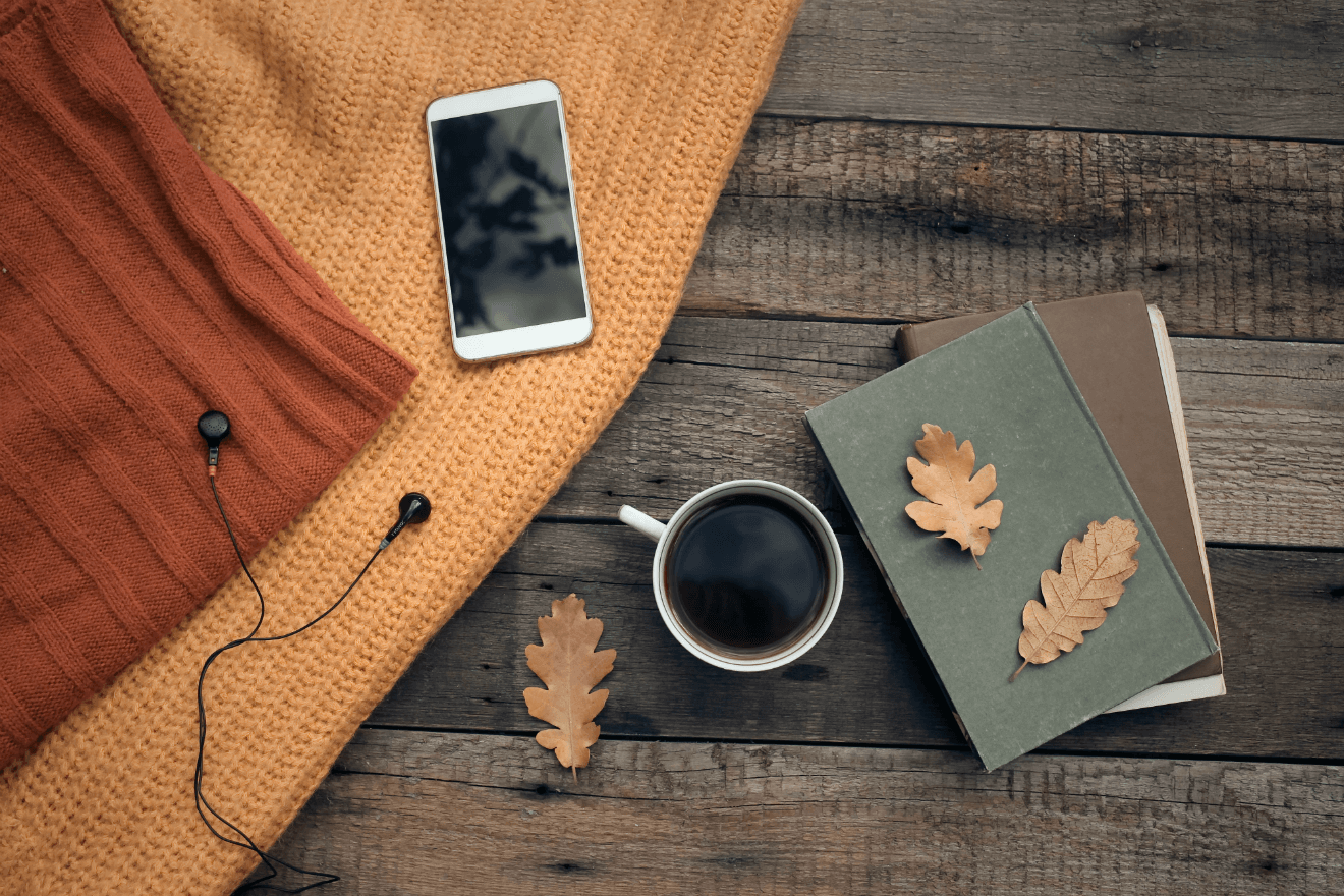 fall playlist phone earbuds coffee leaves notebooks