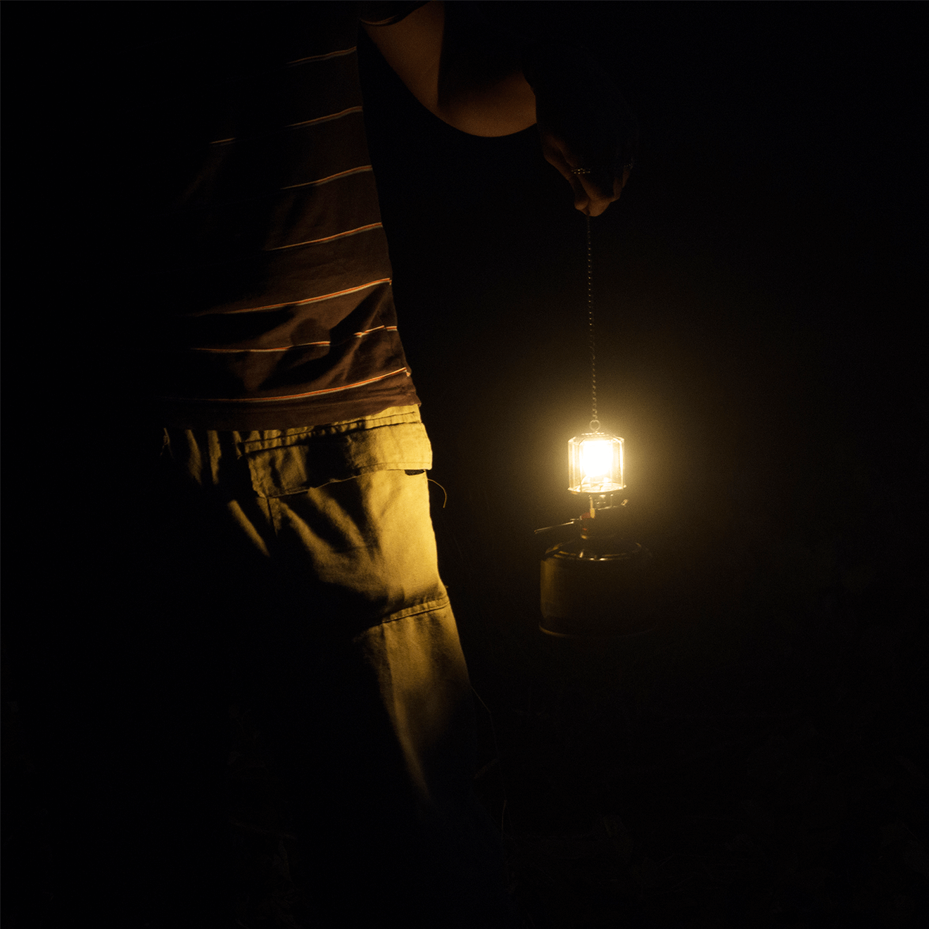 man holding gaslight dark background