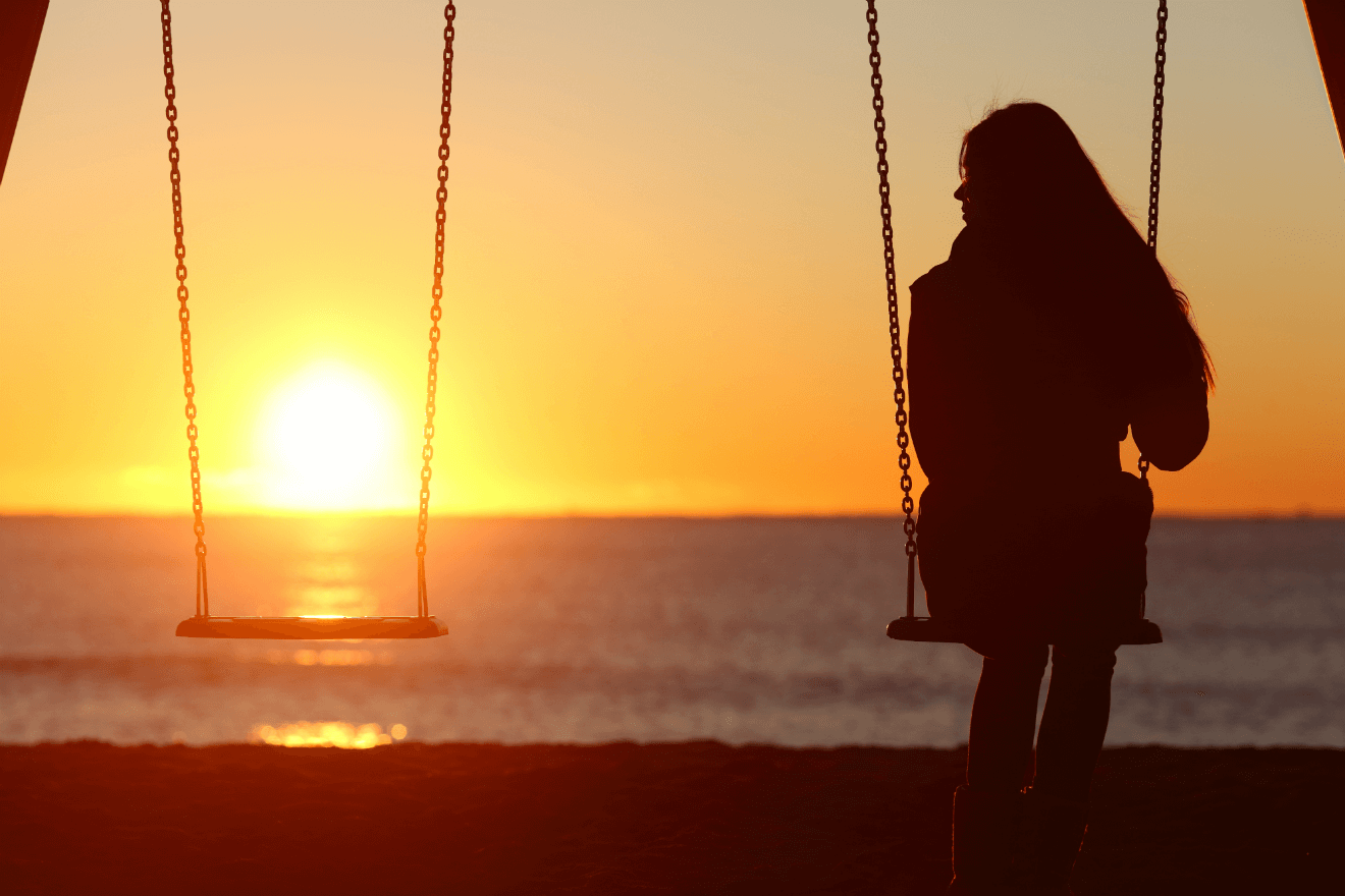 woman alone on swing sunset in background