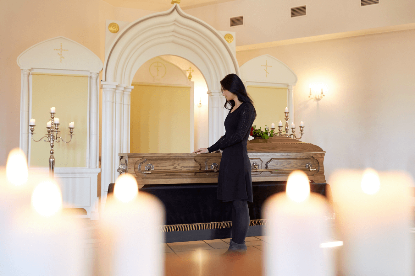 woman grieving funeral casket candles