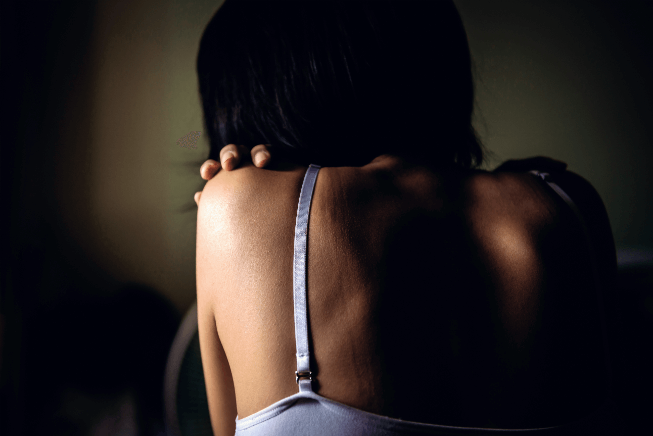 woman with back turned in dark room