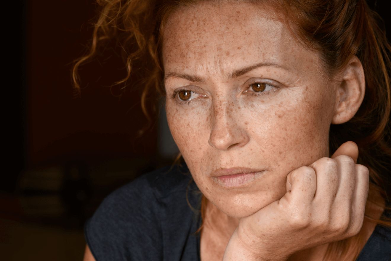 worried red headed woman with hand on chin
