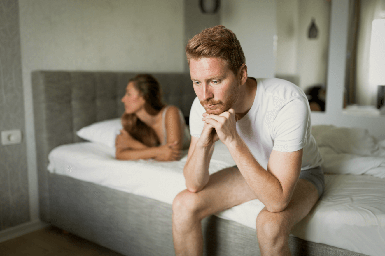 man woman in bed depressed