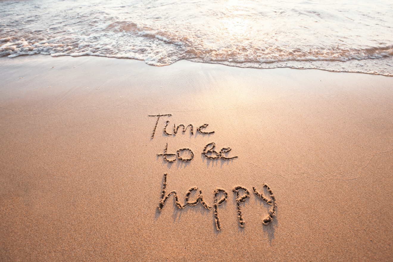 time to be happy written in beach sand wave behind