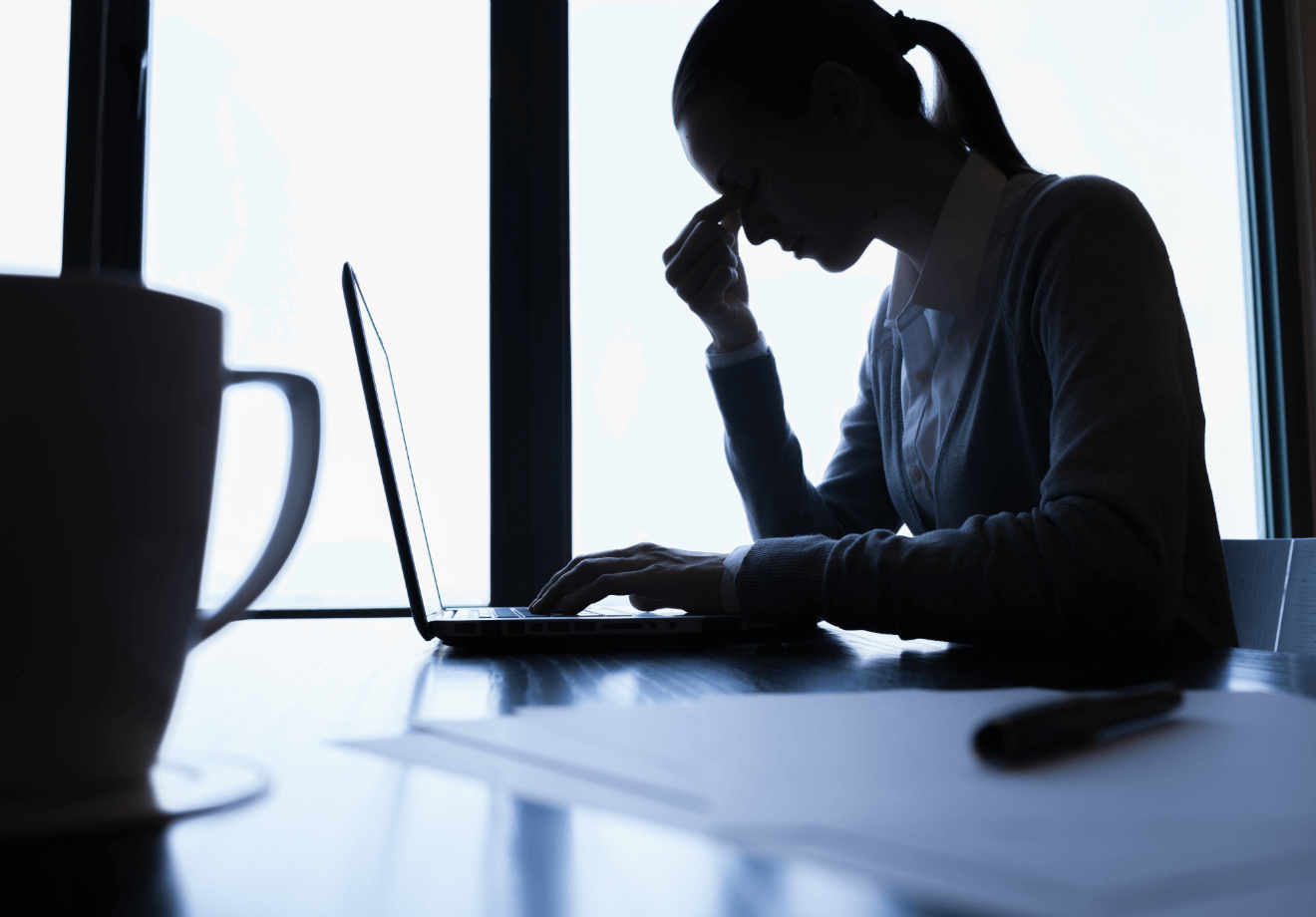 depressed woman working on laptop coffee mug
