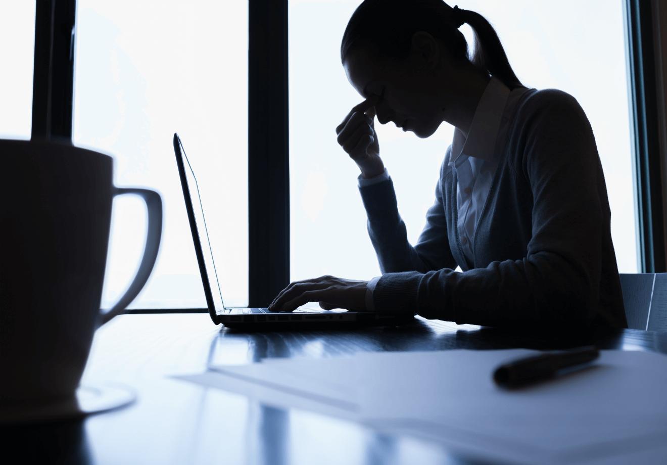 depressed woman working on laptop coffee mug