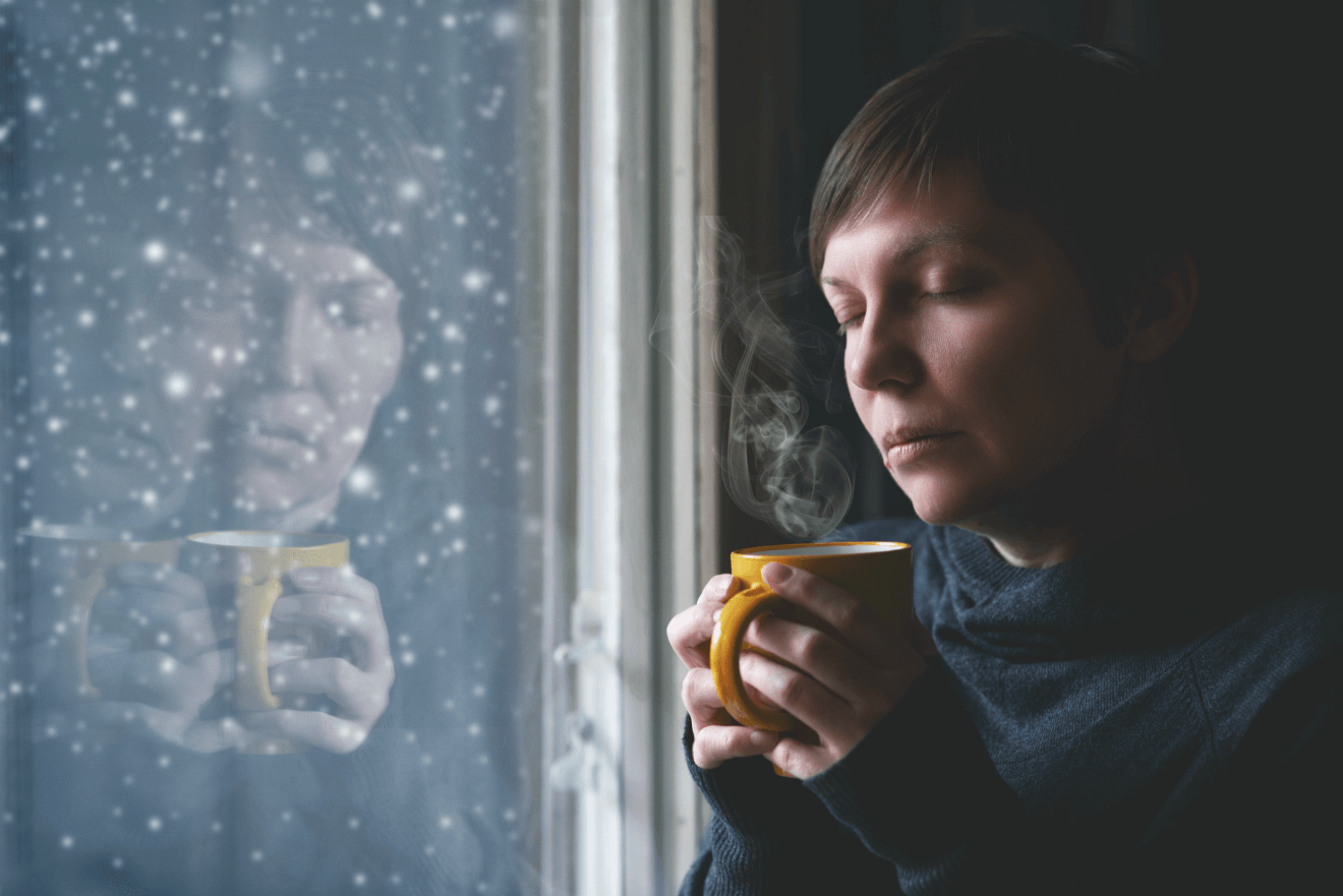 woman holding coffee mug during winter snowing