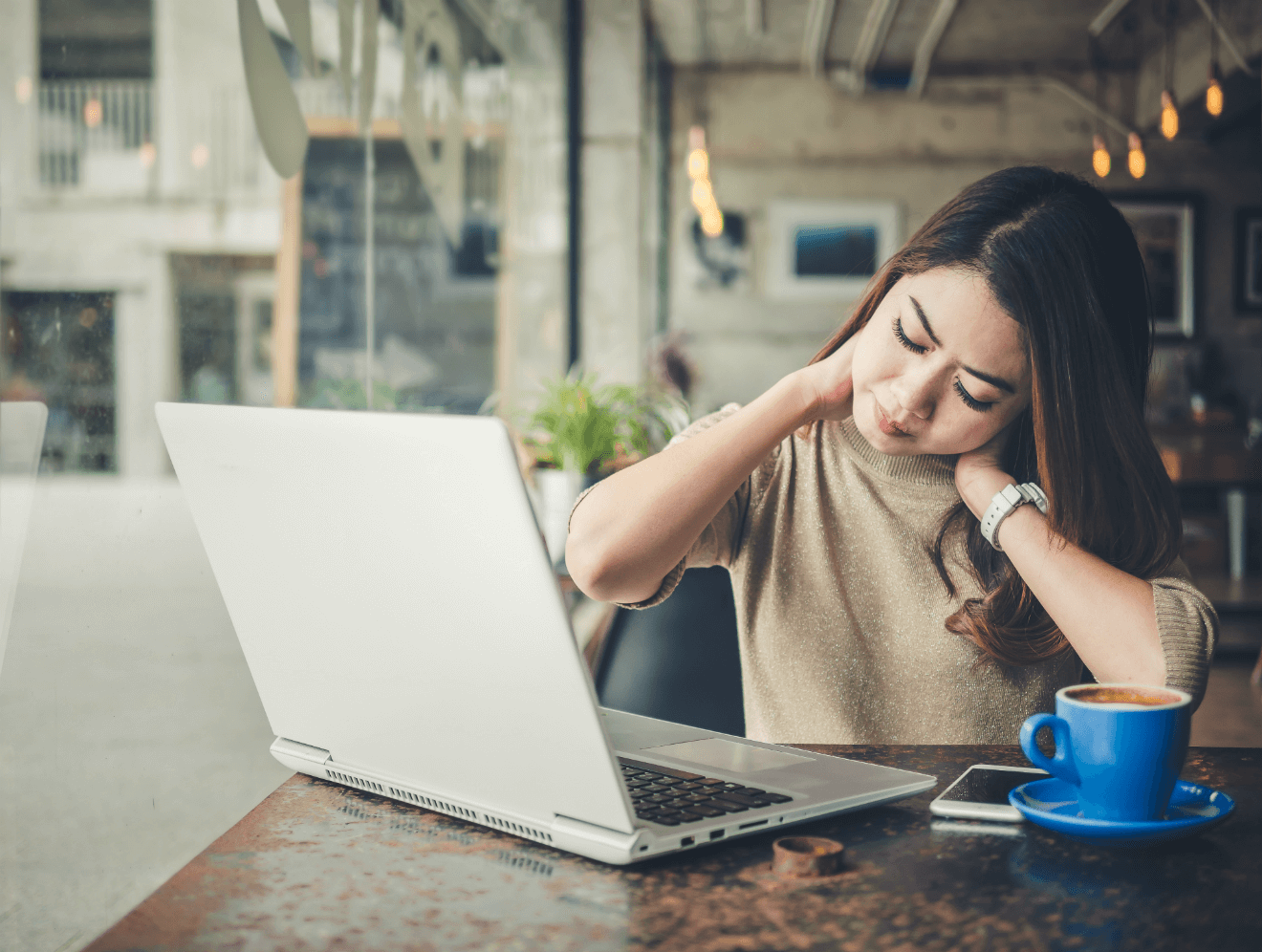 stressed sore woman working on computer at cafe