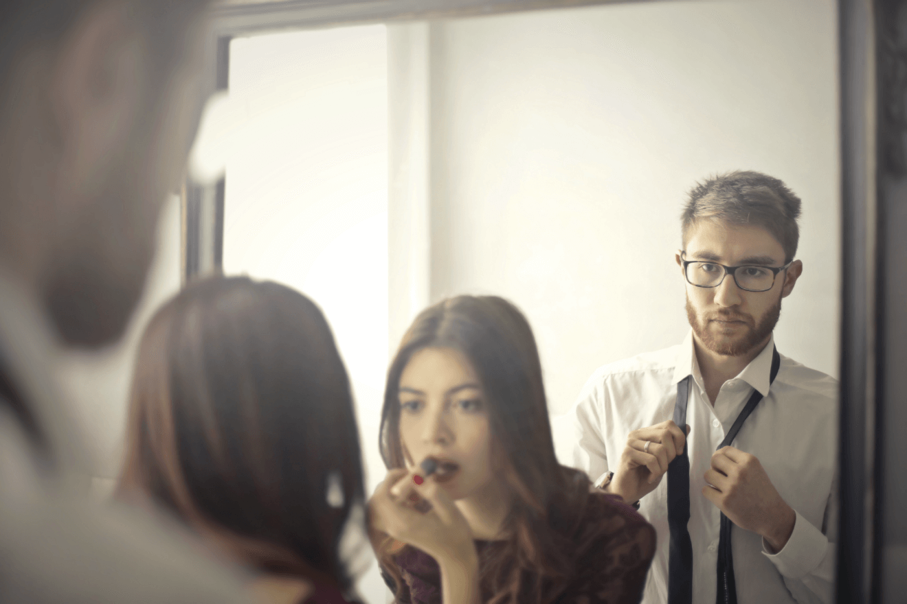 woman putting on lipstick man getting dressed before going out