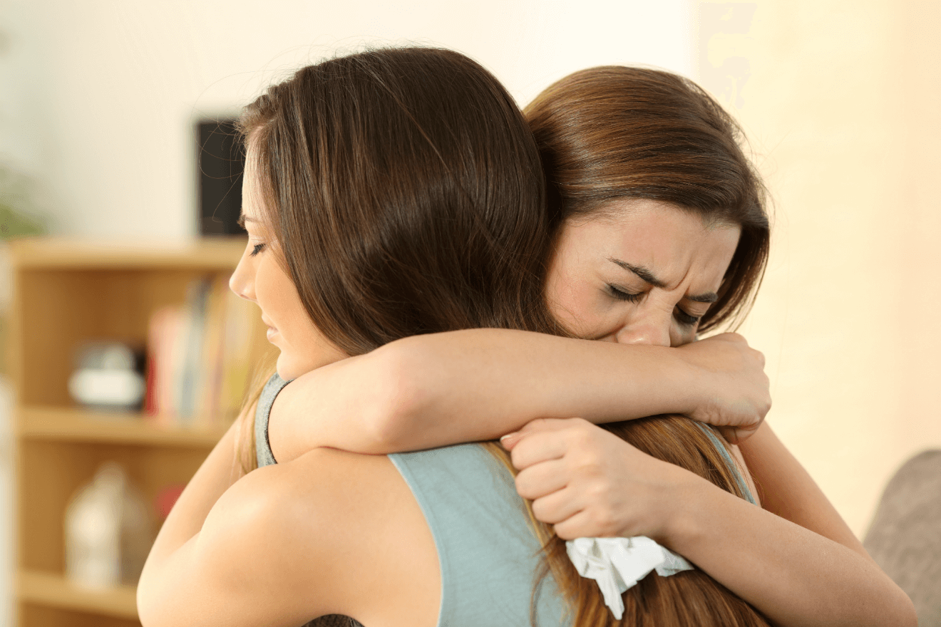woman hugging comforting her crying friend