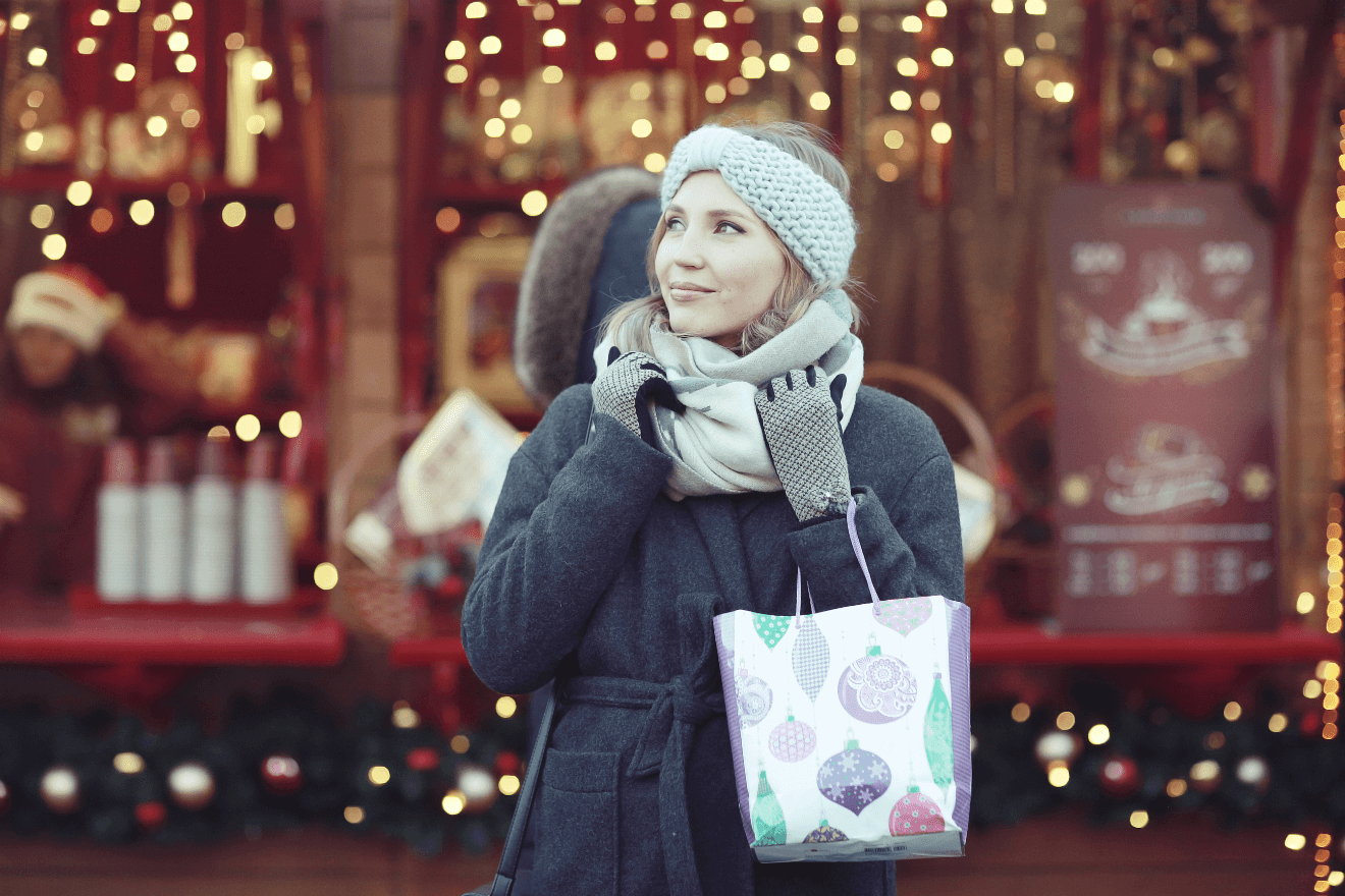 woman outside in coat holiday shopping
