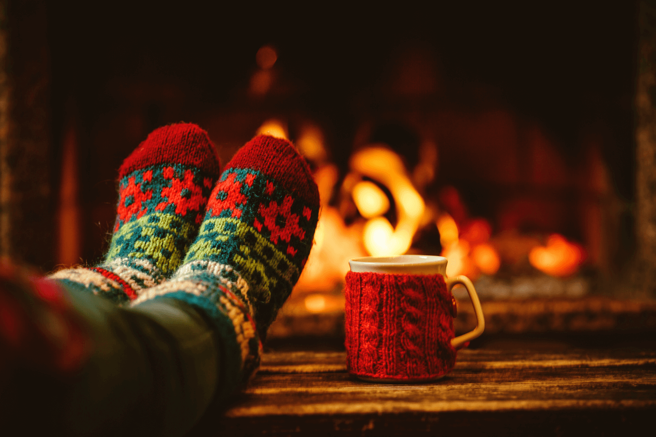 woman with christmas socks and mug relaxing by fireplace