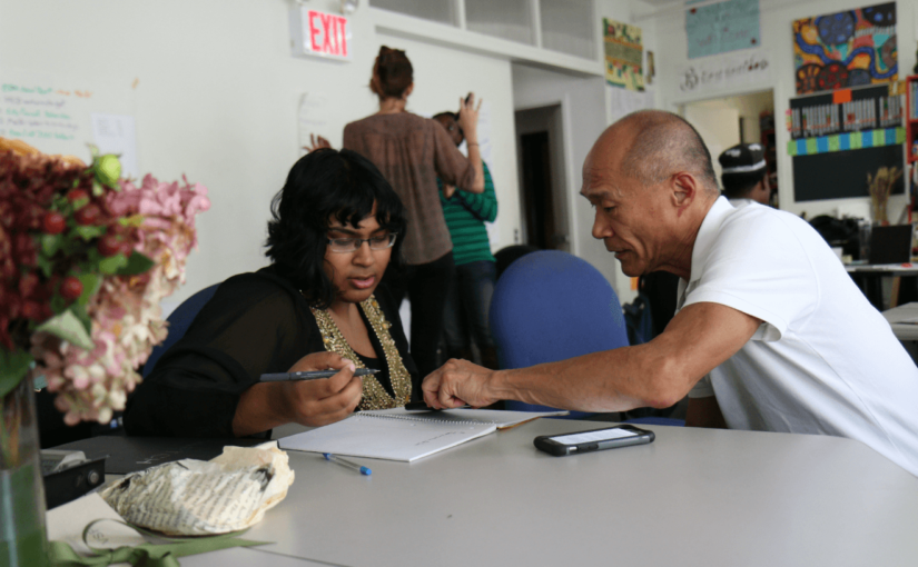 black woman asian man coordinating activism efforts on table