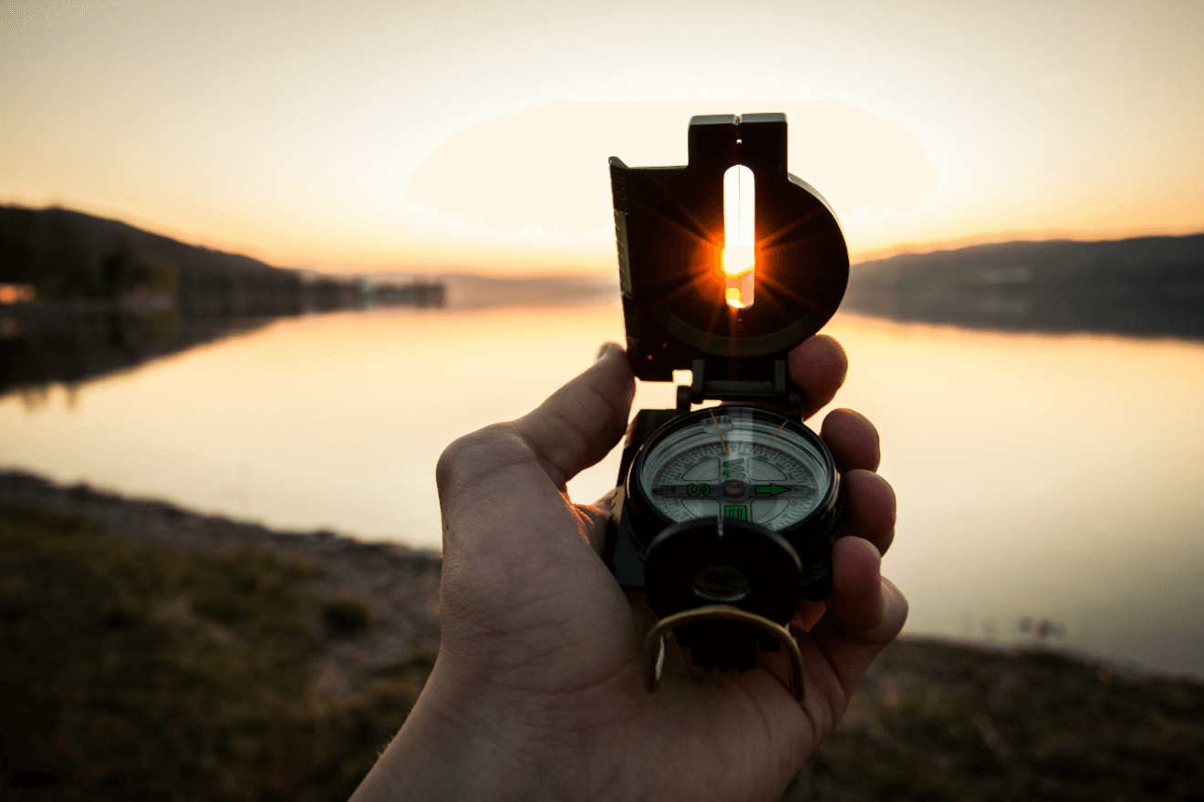 compass facing a lake at sunset