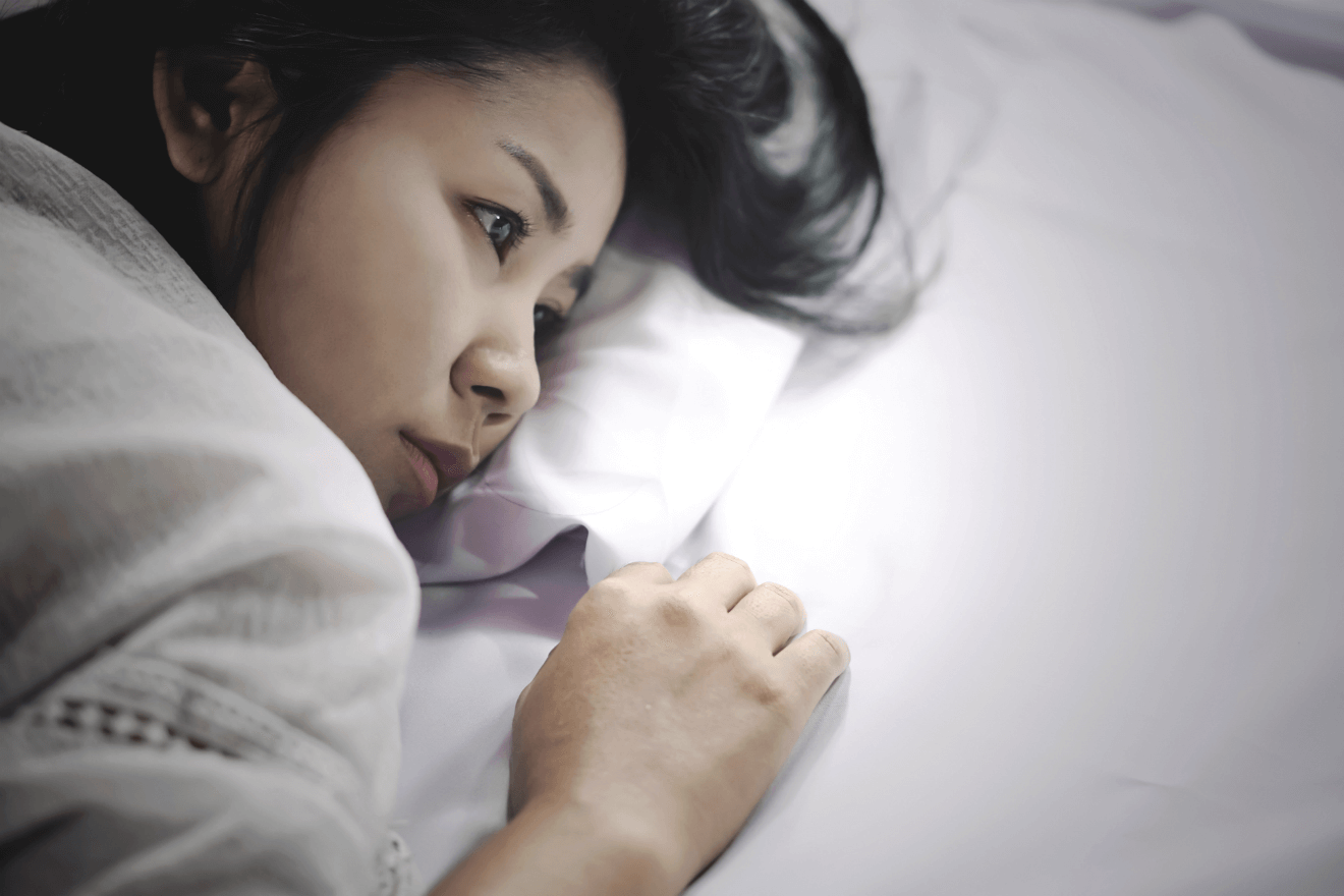 Asian woman depressed in bed