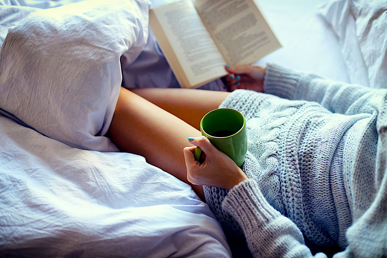Person reading with tea under covers