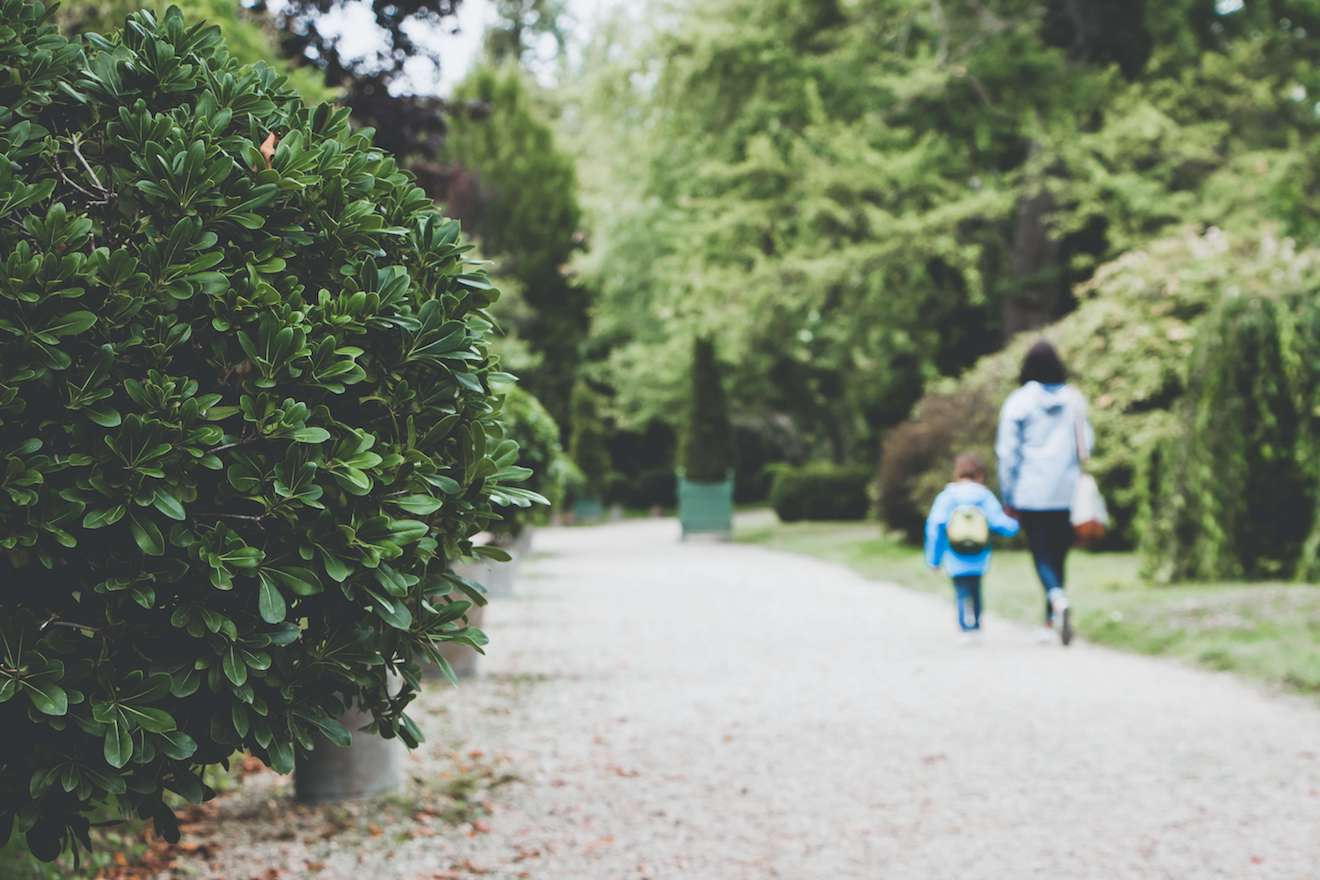 Mother and son strolling on green path in spring