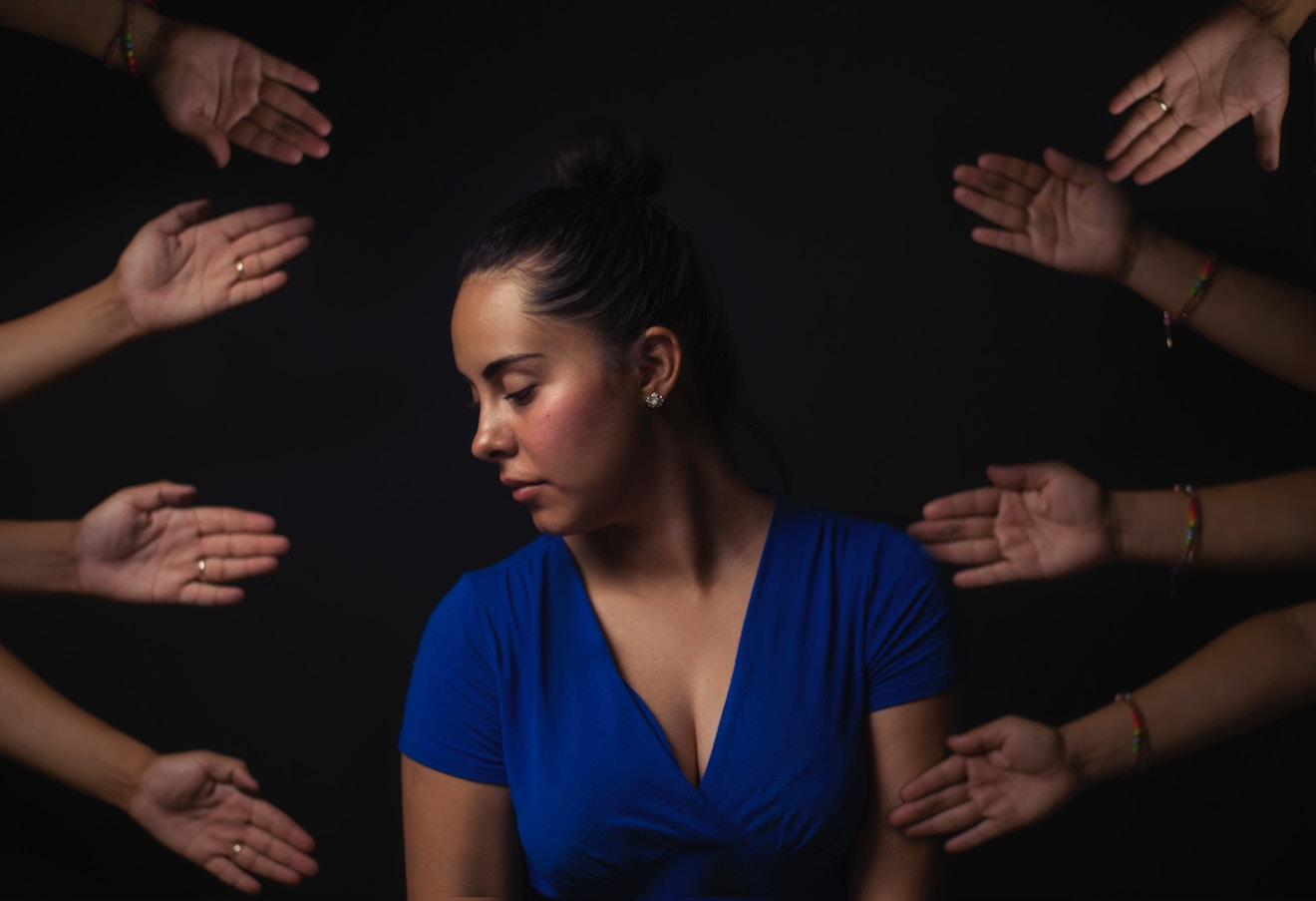 Woman looking away surrounded by helpful hands