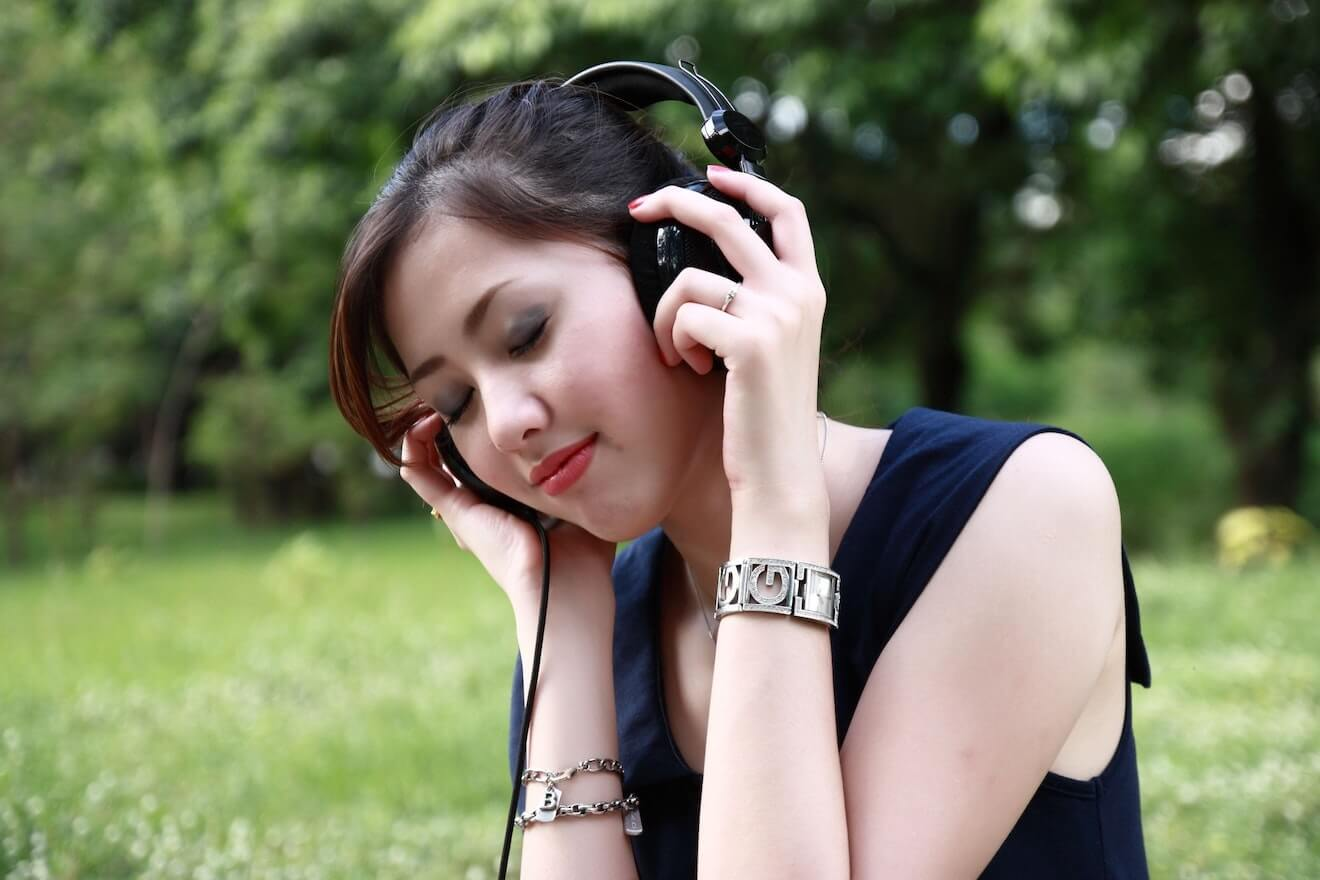 Woman in park with headphones