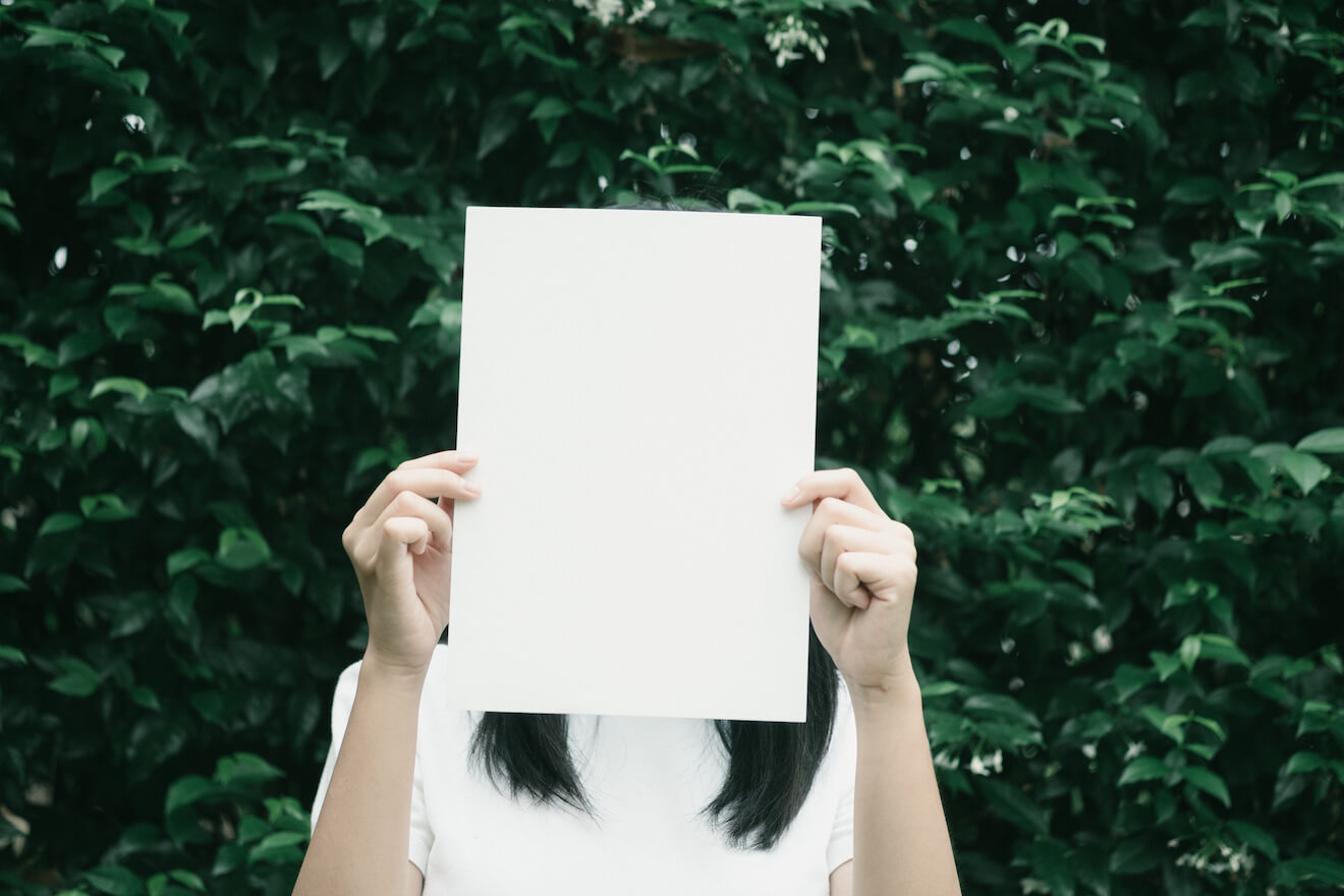 Woman with blank paper in front of face