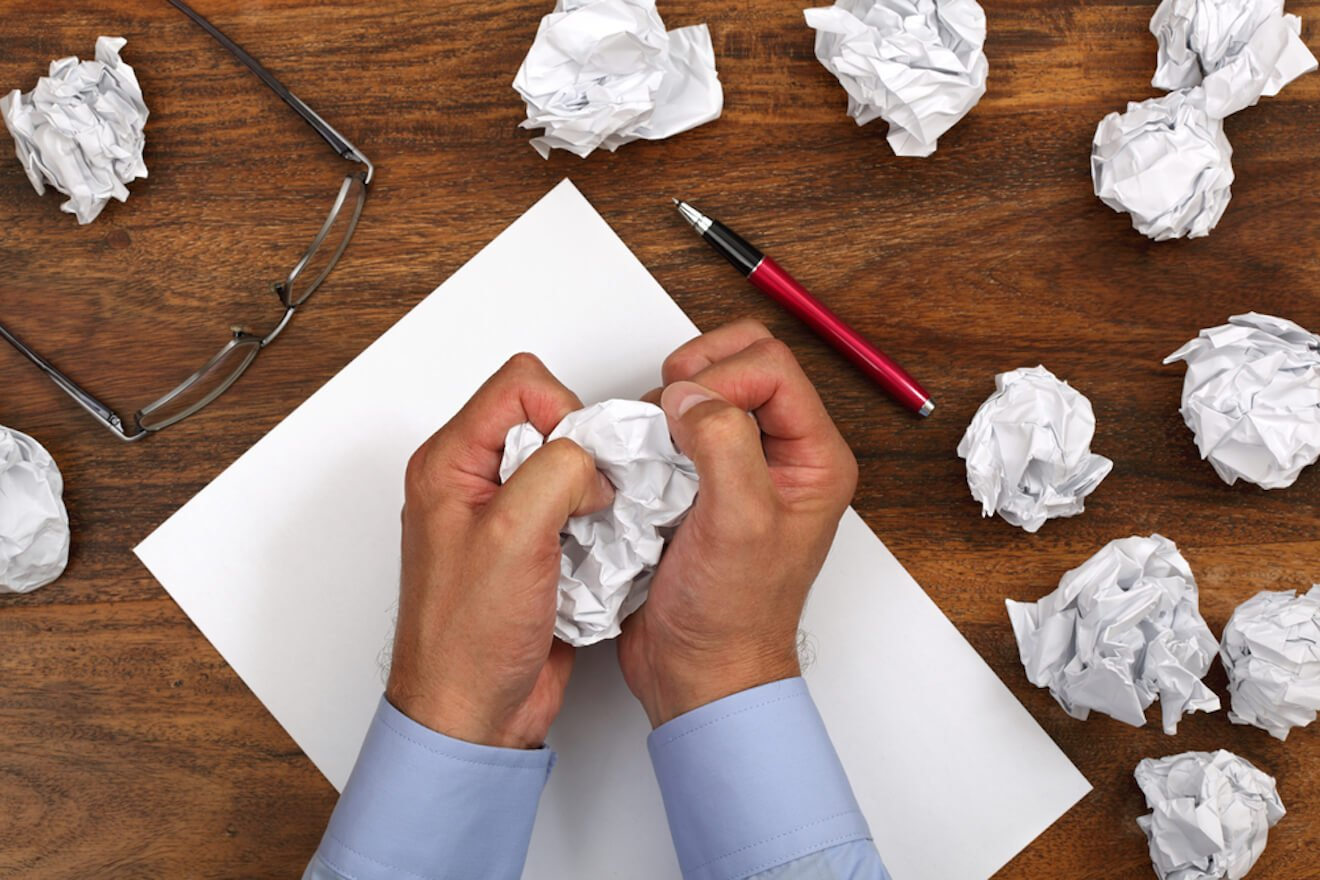 Frustrated person writing unsuccessfully