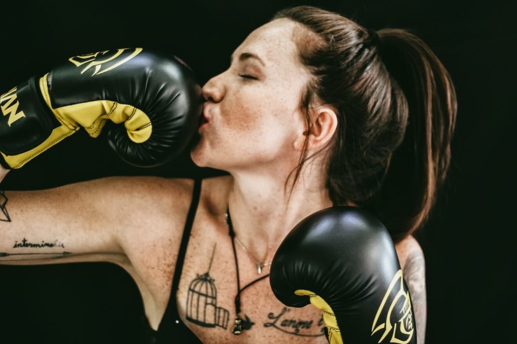 Smiling woman kissing boxing gloves