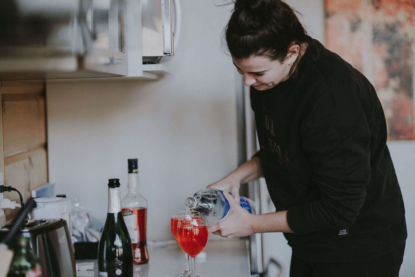 Woman pouring a drink in the kitchen