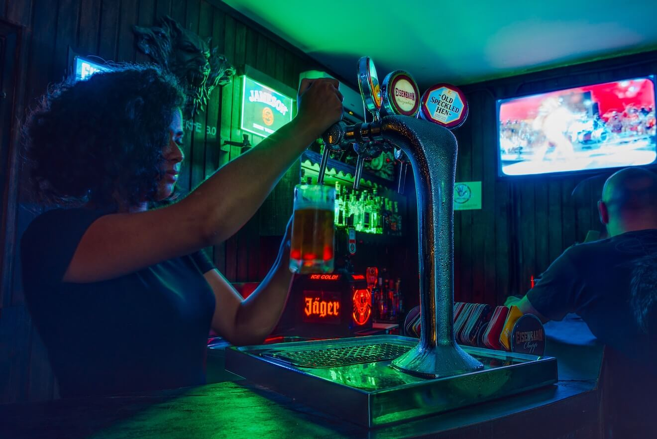 Bartender pouring a drink at a dive bar