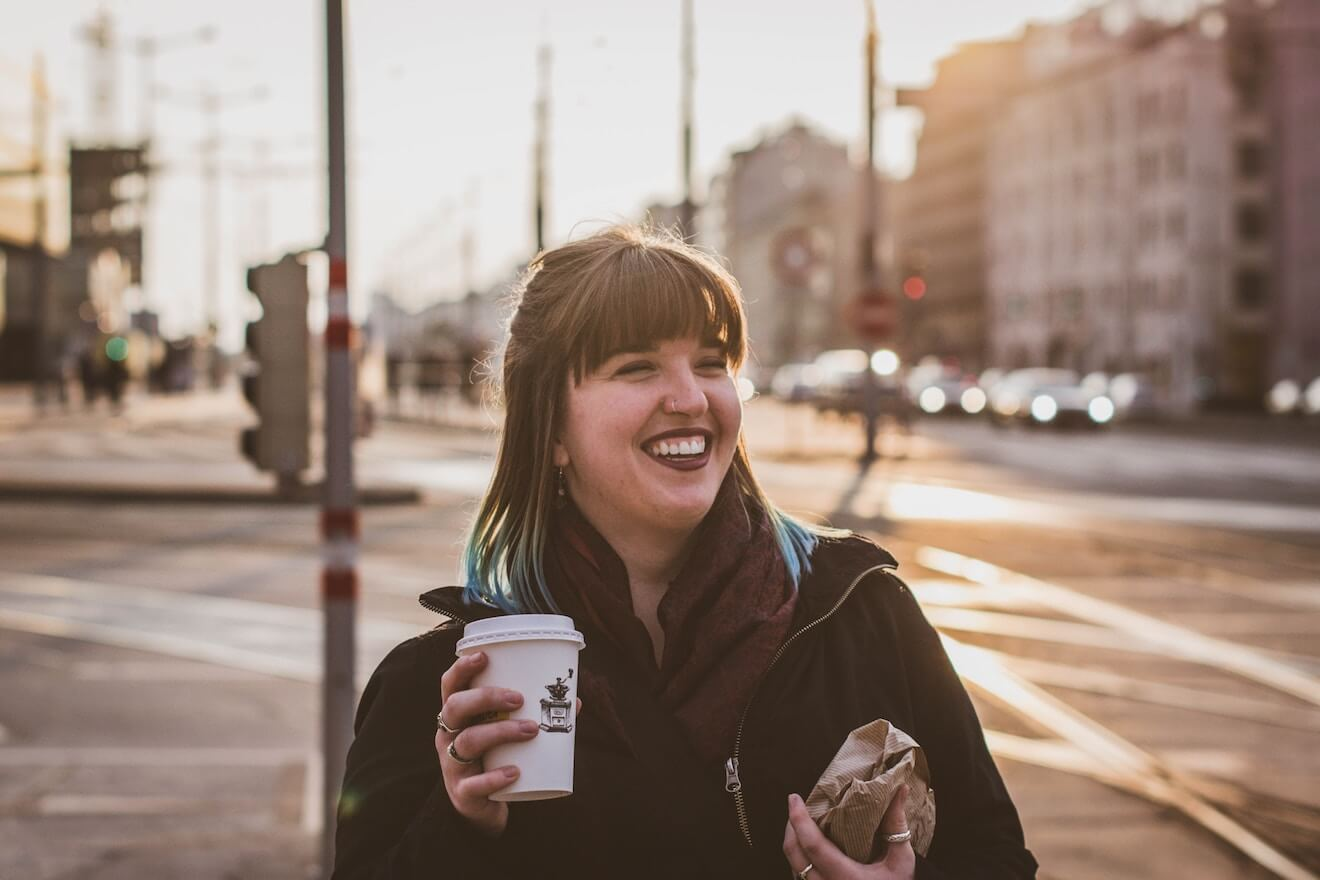 Woman smiling on street with coffee and bagel
