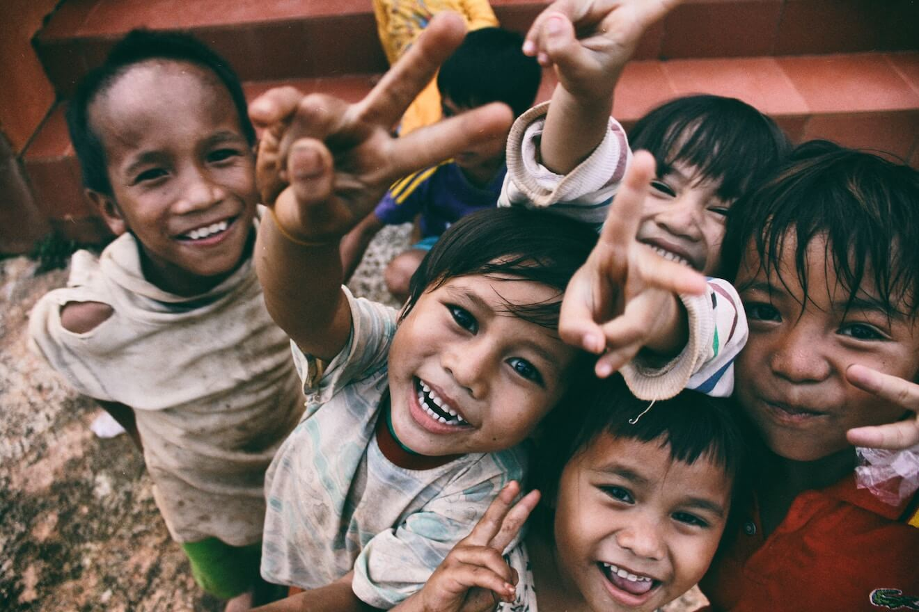 Children smiling and giving the peace sign