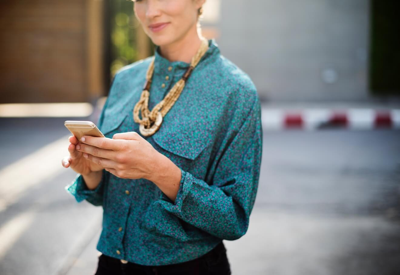 Woman in teal shirt smiling while using her phone