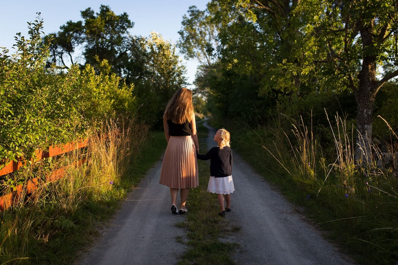 Mother and daughter walk on a path at dusk