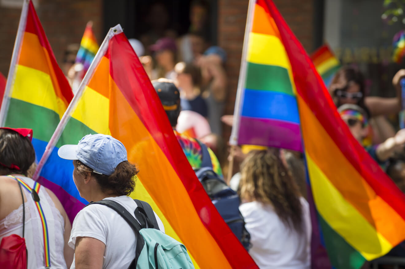 People marching in gay pride parade with rainbow flags