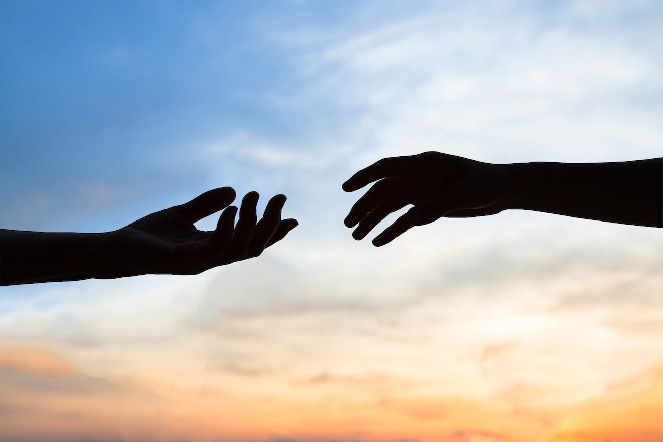 Hands reaching out to each other with a sunset background