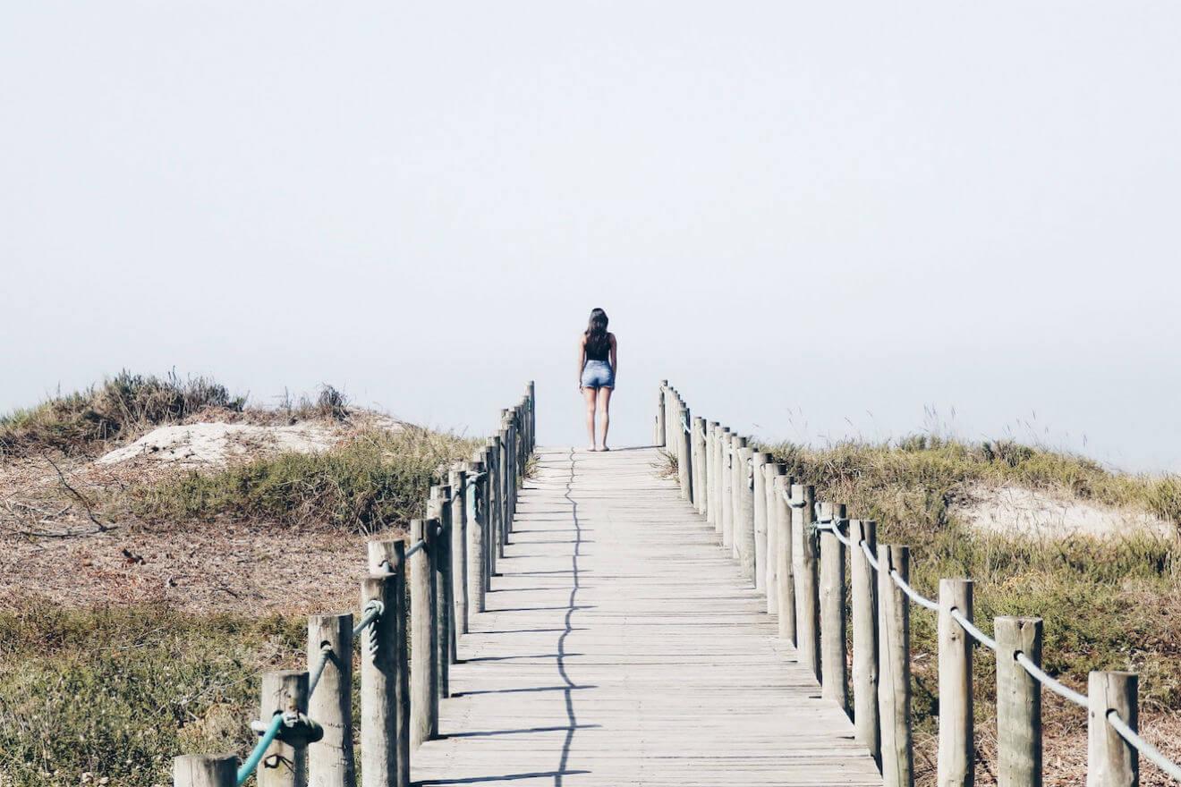 Woman walking long path leading up to beach