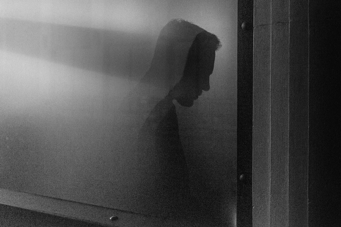 A man's silhouette behind a screen in black and white