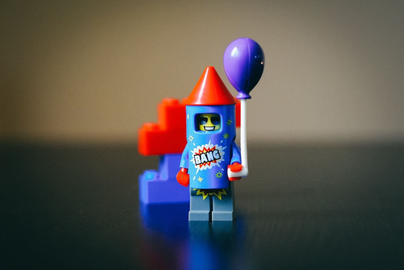 A Lego rocketman holding a balloon